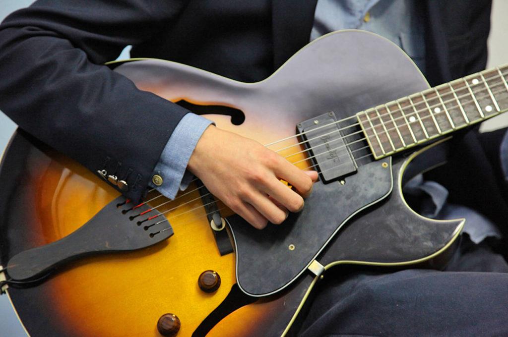 Gros plan mains sur une guitare Sciences techniques théâtre musique danse S2TMD bac lycée enseignement supérieur Fénelon groupe scolaire Estran Brest