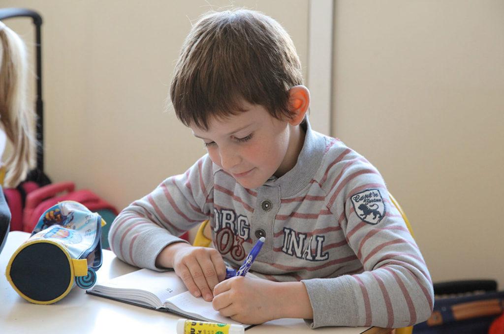 Élève écrit cahier école maternelle primaire élémentaire éducation enseignement épanouissement élèves Saint Joseph du Pilier Rouge Brest