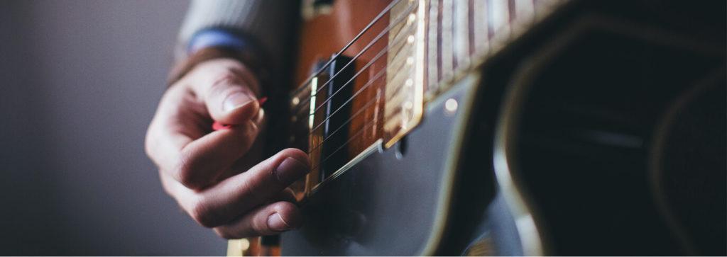 Gros plan zoom sur une main qui joue de la guitare cordes instrument Sciences techniques théâtre musique danse S2TMD bac lycée enseignement supérieur Fénelon groupe scolaire Estran Brest