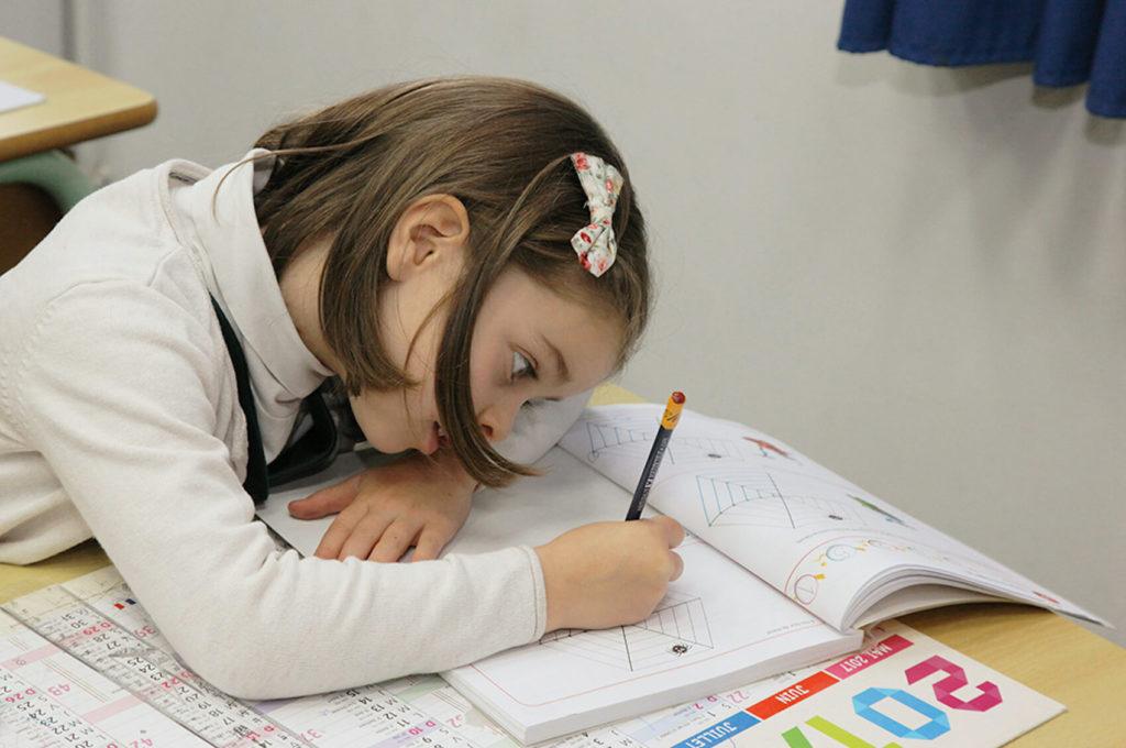 Petite fille écrit cahier concentration école maternelle primaire élémentaire éducation enseignement épanouissement élèves Immaculée Conception Brest