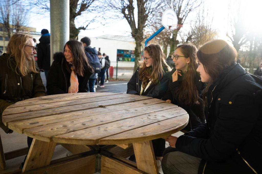 Élèves souriants autour d'une table dans la cour récréation pause école collège lycée Charles de Foucauld Brest enseignement éducation © MarcGlenPhotographie