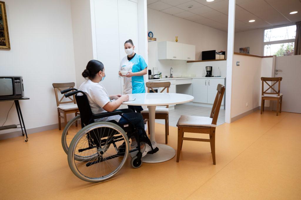 Femme fauteuil roulant à table soins à domicile BAC PRO ASSP Estran ©MarcGlenPhotographie