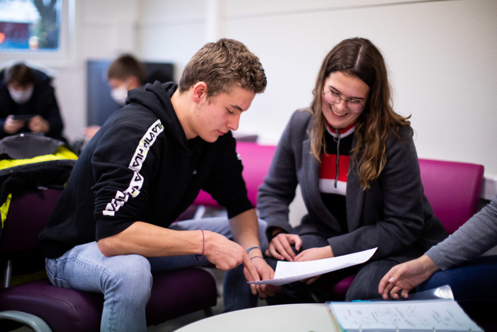 Élèves souriants autour d'un cahier étude enseignement école collège lycée supérieur Charles de Foucauld Brest ©MarcGlenPhotographie
