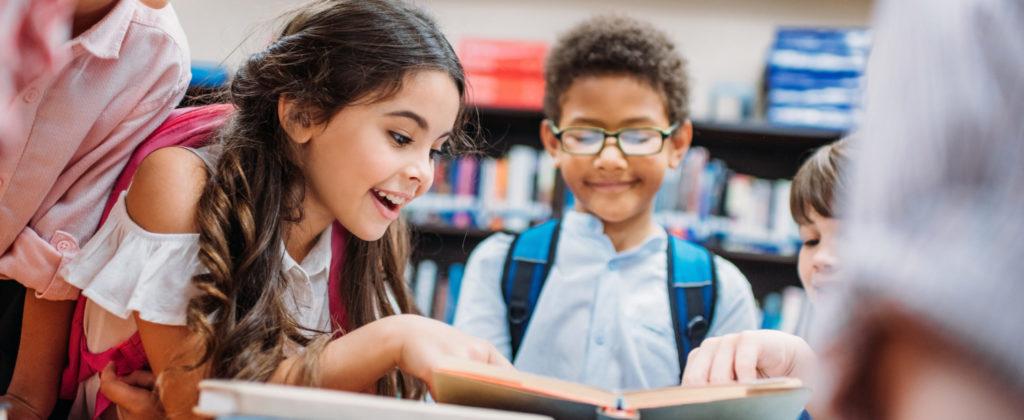 Enfants regardant un livre souriant élèves école éducation enseignement